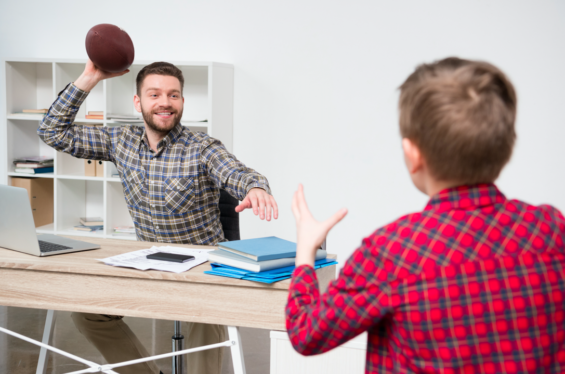 dad and son play football work from home